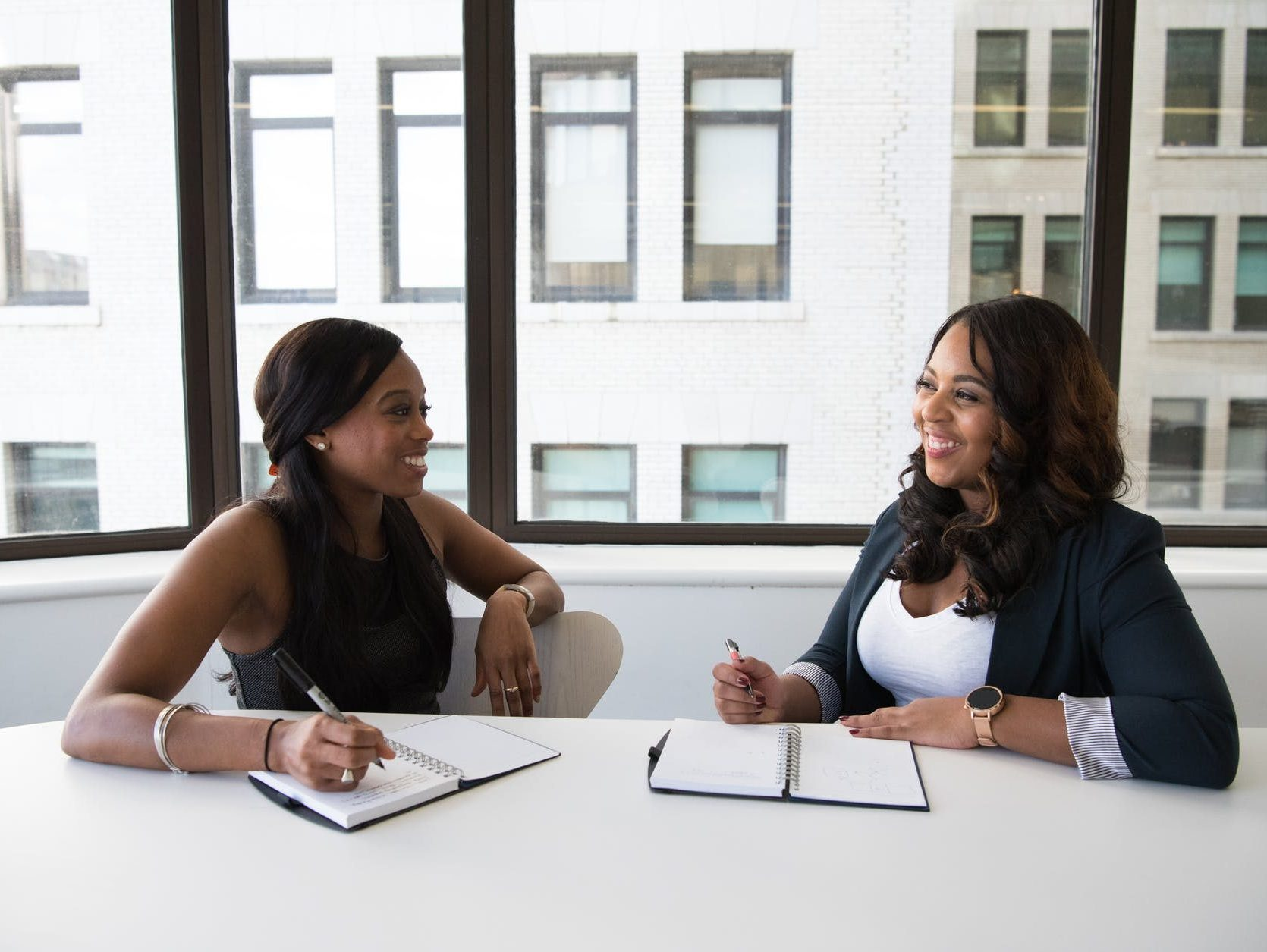 Two Black people with long hair in casual business attire sit at a table in front of a window, they are smiling at each other. On the table in front of each person are two notebooks . The people hold pens as if preparing to write.
